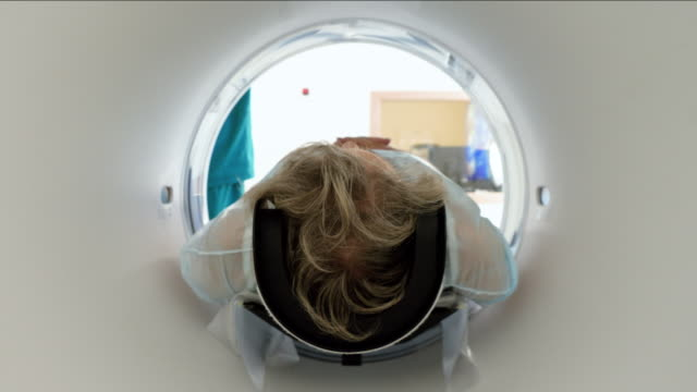 Close-up shot of a female mature patient lying on a table of CT scan machine. Computer tomograph scanning body and brain of elderly woman. High-tech equipment in medical clinic. 4K Modern equipment in hospital. Female elderly patient is on medical examination on magnetic resonance imaging or computed tomography scan. 4K radiologist stock videos & royalty-free footage
