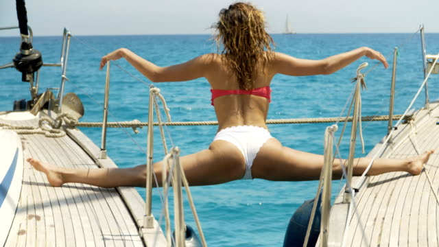 Close-up Shot of a Fit Young Woman Doing Yoga on a Sailing Yacht. In the Background Beautiful Calm Sea and Clear Sunny Sky Close-up Shot of a Fit Young Woman Doing Yoga on a Sailing Yacht. In the Background Beautiful Calm Sea and Clear Sunny Sky yachting stock videos & royalty-free footage