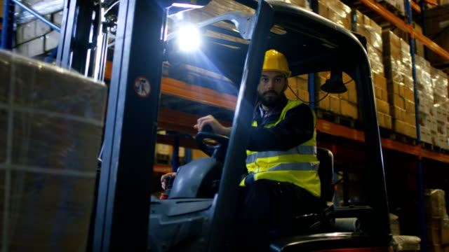 Close-up Shot of a Forklift Driver Operating Vehicle in a Big Warehouse full of Pallet Rack. Close-up Shot of a Forklift Driver Operating Vehicle in a Big Warehouse full of Pallet Rack. Shot on RED EPIC-W 8K Helium Cinema Camera. forklift stock videos & royalty-free footage