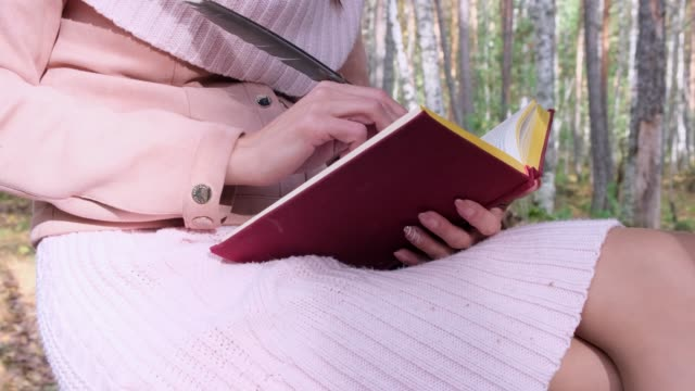 close-up shot of a girl in the autumn forest, a female hand writes with a pen in a book. A woman sits near a tree in the autumn forest and holds a book in her hands