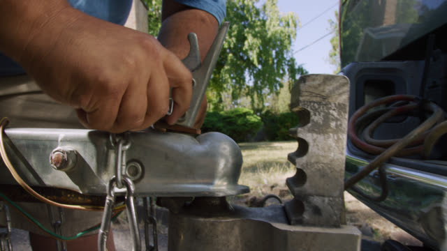 close-up shot of a hispanic man's hands attach a trailer coupler with a latch to the ball hitch on his vehicle on a sunny day - rimorchiatore video stock e b–roll
