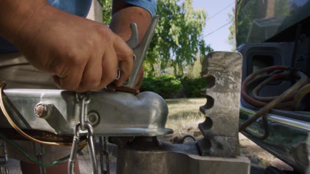 närbild skott av en spansktalande mans händer bifoga en trailer coupler med en spärr till ball hitch på hans fordon på en solig dag - maskindel bildbanksvideor och videomaterial från bakom kulisserna