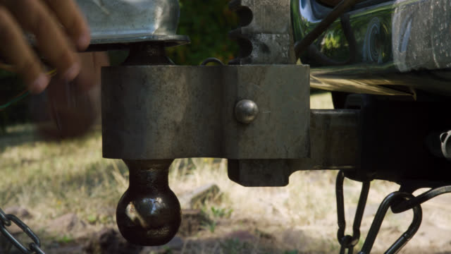 close-up shot of a hispanic man's hands closing the latch on the trailer coupler, attaching the safety chains, and installing the coupler pin before hooking up the electrical to his vehicle on a sunny day - rimorchiatore video stock e b–roll