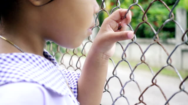 Close-up shot of a little girl hand holding iron fence video