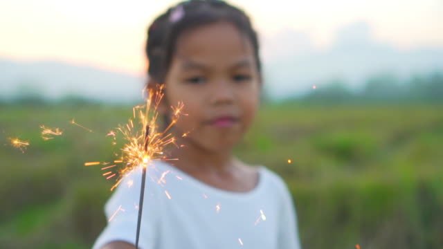 Close-up shot of a little girl holding a burning sparkles in field at evening