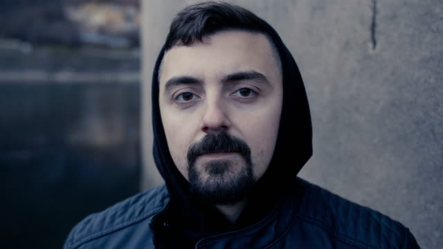 Close-up shot of a man with hood looking at camera with serious facial expression video