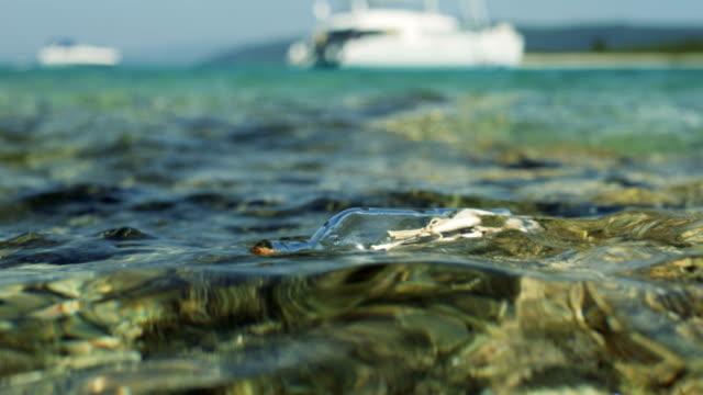 närbild skott av ett meddelande i flaskan, drivande i grunt hav med vita yacht i bakgrunden. - map oceans bildbanksvideor och videomaterial från bakom kulisserna