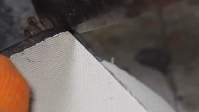 Close-up shot of a metal guillotine cutting cardboard in a small furniture factory. Master working in orange protective gloves.  Slow motion 50 fps 4k