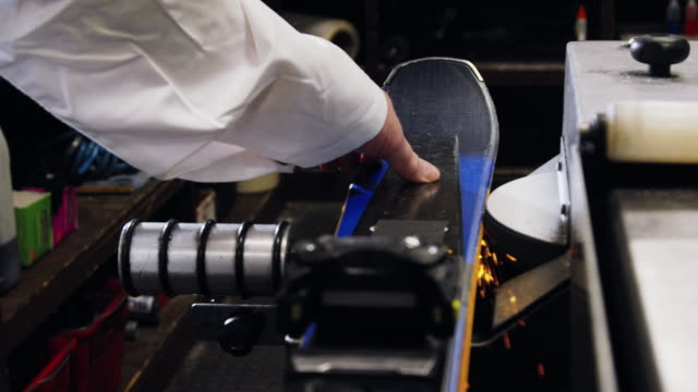 close-up shot of a ski technician using a belt grinder to sharpen the edges of downhill skis as sparks fly in an indoor repair shop - negozio sci video stock e b–roll