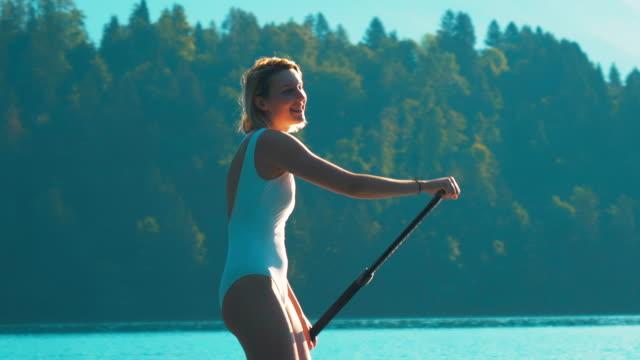 stockvideo's en b-roll-footage met een close-up shot van een lachende jonge vrouw in een witte badmode is peddelen op een stand-up peddel in het midden van het meer op een mooie zomer ochtend. - paddle