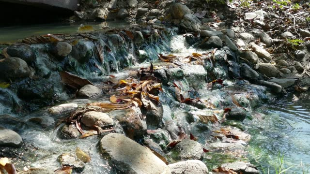 Close-up shot of a stream as it falls over rugged stones in Chiang Mai Thailand.