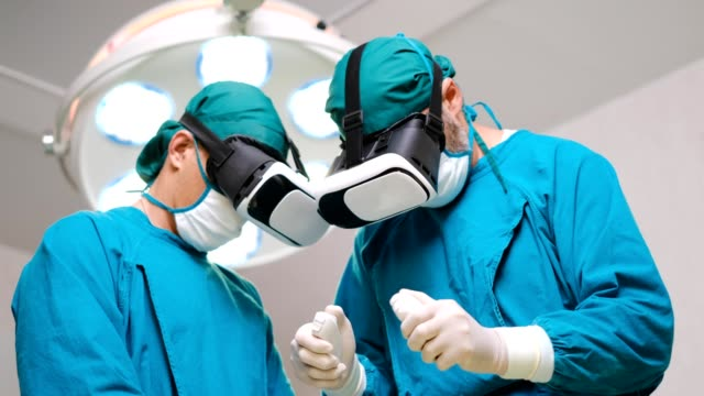 Close-up Shot of a Surgeon Putting on Augmented Reality Glasses to Perform State of the Art Surgery in High Tech Hospital. Doctors and Assistants Working in Operating Room.