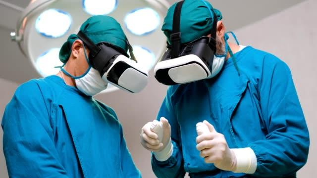 vídeos de stock, filmes e b-roll de close-up shot de um cirurgião colocando óculos de realidade aumentada para realizar cirurgia de última geração no hospital high tech. médicos e assistentes trabalhando na sala de cirurgia. - exame médico procedimento médico