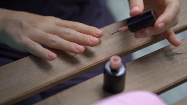 nahaufnahme einer frau, die ihre maniküre mit gellackmacht macht, die unter ultraviolettem licht aushärtet - fingernagel stock-videos und b-roll-filmmaterial