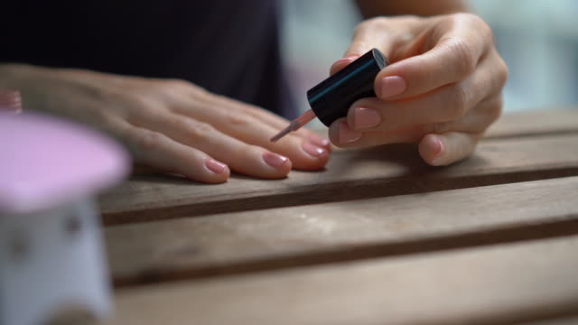 Closeup shot of a woman doing her manicure using gel polish that hardens under ultraviolet light