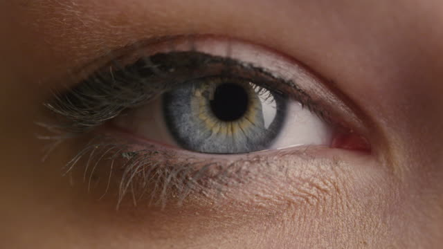 close-up shot of a woman opening her blue eyes with light day make-up and focusing them. - vicino video stock e b–roll