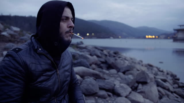 Close-up shot of a young depressed man sitting on lake shore contemplating and smoking cigarette