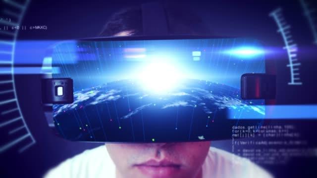 VR kulaklık giyen ve sanal gerçeklik yaşayan genç bir adamın yakın çekim çekimi video