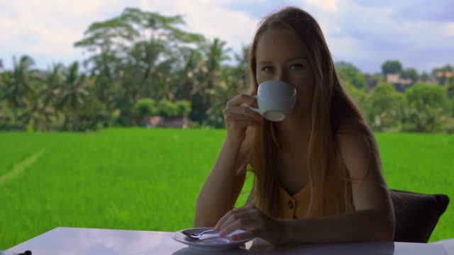 Closeup shot of a young woman drinking tea or coffee in a rural cafe with a rice field at a background