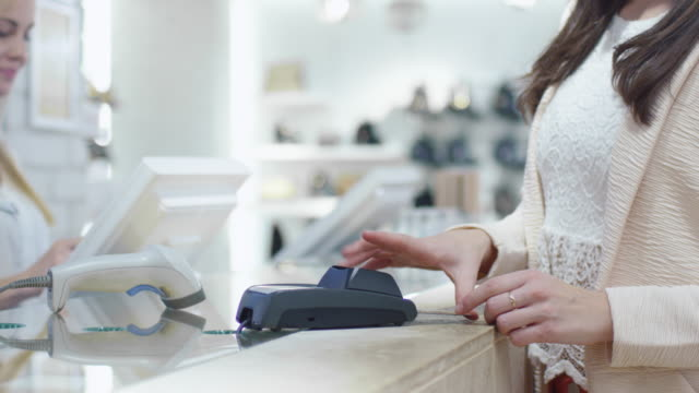 Close-up shot of a young woman that is paying with a card at the cash desk in a department store. video