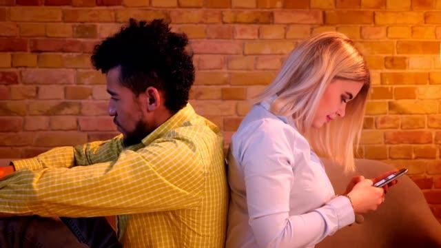 nahaufnahme von afrikanischen kerl und kaukasischen mädchen sitzen zurück zu hinten auf dem sofa beobachten in ihre smartphones zu hause. - rücken an rücken stock-videos und b-roll-filmmaterial