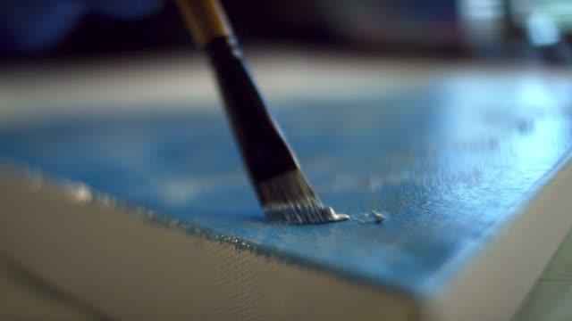 vidéos et rushes de coup de gros plan d'une artiste tamponnant peinture à l'huile sur une toile dans un studio d'art d'intérieur - toile à peindre