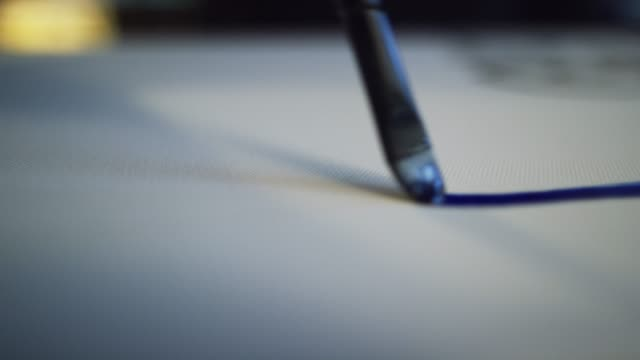 Close-Up Shot of an Artist Painting a Thin Line of Blue Oil Paint on a Canvas with a Paintbrush