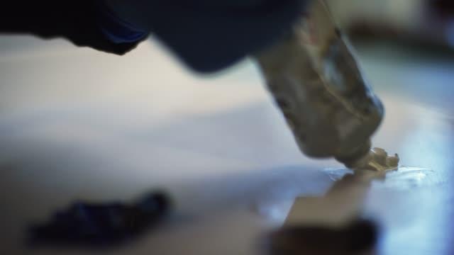 primo piano di un artista che indossa guanti protettivi e spreme la vernice ad olio bianco da un tubo a una tavolozza d'arte - immergere video stock e b–roll