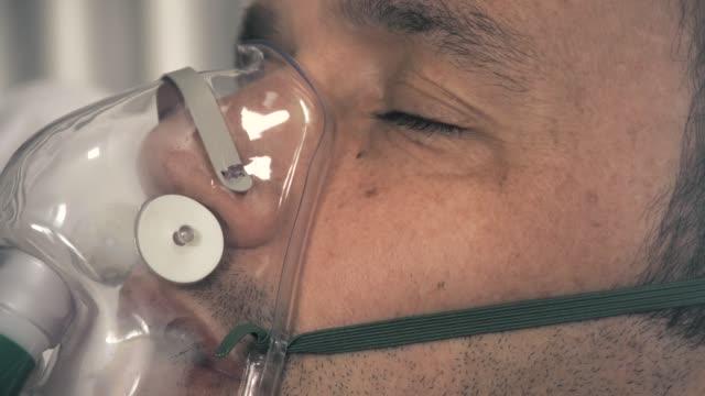 nahaufnahme eines infizierten covid-19-infizierten mannes, der ein beatmungsgerät trägt, um beim atmen zu helfen. - sauerstoff stock-videos und b-roll-filmmaterial