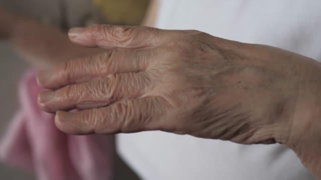 närbild skott av en gammal kvinna darrande hand med tremor - ancient white background bildbanksvideor och videomaterial från bakom kulisserna