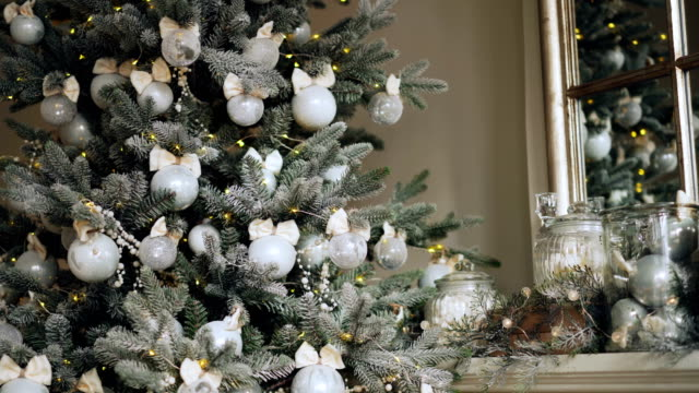 close-up shot of awesome artificial new year tree with beautiful silver balls hanging on its branches and lights glittering on fir-tree. decorated mantel is visible. - perfezione video stock e b–roll