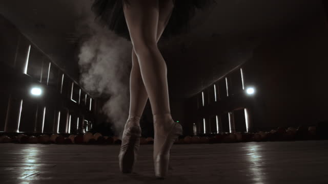 vídeos de stock e filmes b-roll de close-up shot of ballerina's legs. she dances on her pointe ballet shoes. she's wearing black tutu dress. shot in a bright and sunny studio. in slow motion - going inside eye