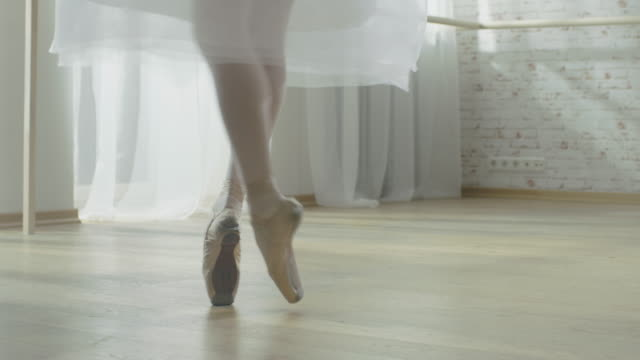 nahaufnahme schuss von ballerinas beine. sie tanzt und dreht auf ihren pointe ballet shoes. she es wearing white tutu dress. erschossen in einem bright und sunny modern studio. - ballettschuh stock-videos und b-roll-filmmaterial