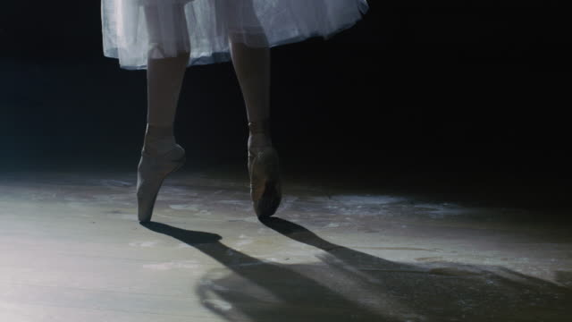 Close-up Shot of Ballerina's Legs. She's Dancing and Spinning on Her Pointe Ballet Shoes in the Spotlight with Darkness Around. She's Wearing White Tutu Dress. '. In Slow Motion. video