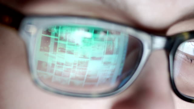 Closeup shot of boy in glasses surfing internet at night video