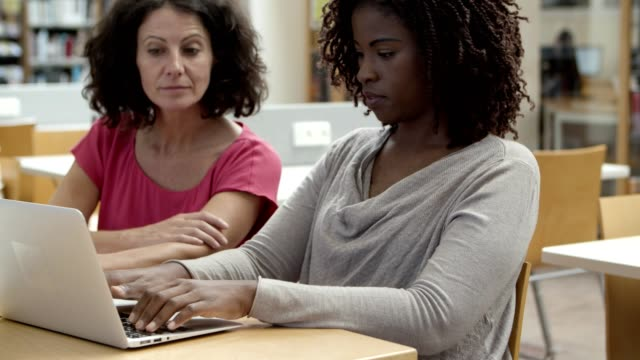 Closeup shot of cheerful women working with laptop at library.