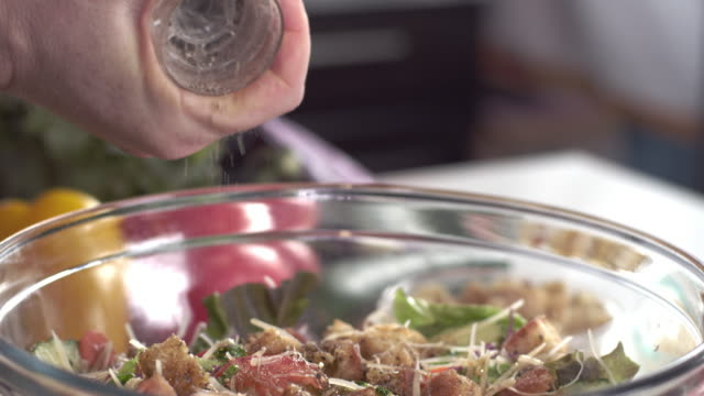 close-up shot of chef grinding black pepper over fresh garden salad - rettificatrice video stock e b–roll