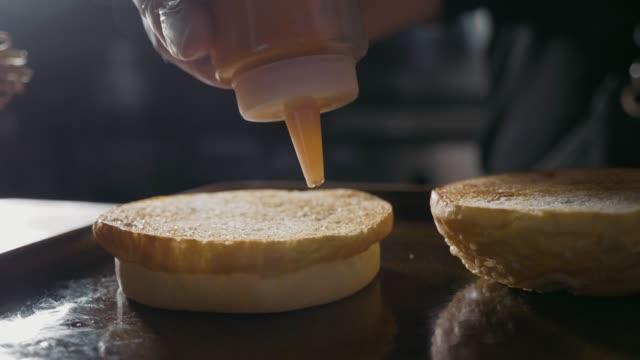vídeos y material grabado en eventos de stock de foto primer plano de manos del chef preparando una hamburguesa, cámara lenta - hamburguesa