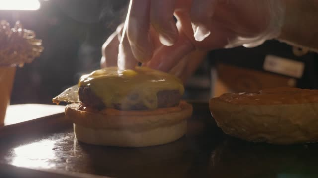 close-up shot of chef's hands preparing a hamburger with beef rissole and cheese - hamburger video stock e b–roll