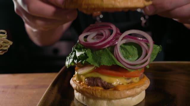 vídeos y material grabado en eventos de stock de foto primer plano de manos del chef preparando una hamburguesa con rissole de carne y queso - hamburguesa