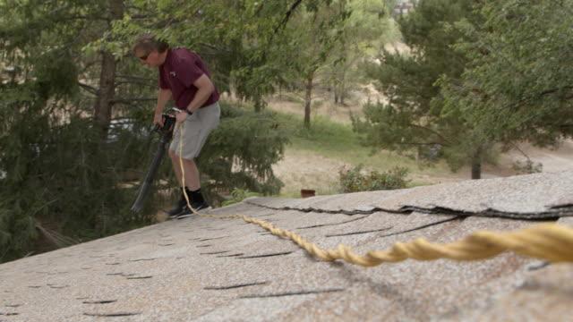 vidéos et rushes de plan rapproché de la photo de cordon sur un souffleur de feuilles électriques pendant qu'il est utilisé pour enlever les graines d'orme, les feuilles et les bâtons des gouttières de toit en aluminium à la maison pour le nettoyage de ressort - vidéos de rallonge électrique