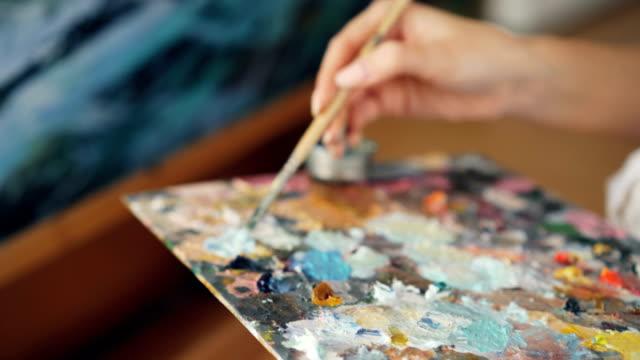 vidéos et rushes de gros plan de sale main féminine tenant pinceau et mélange des couleurs dans la palette puis peinture paysage marin sur la toile. concept art et outils. - toile à peindre