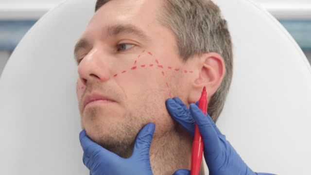 Close-up shot of drawing correction lines on man's face
