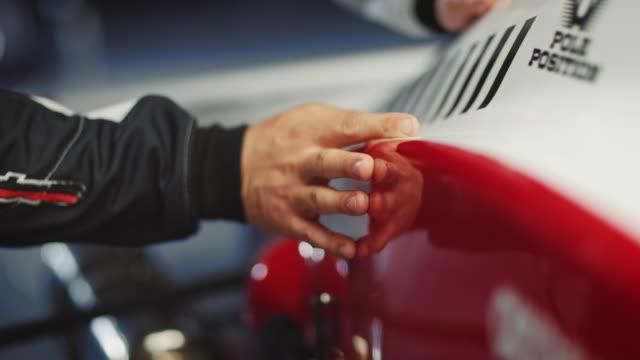 Close-up shot of driver examining body of racecar