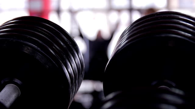 Closeup shot of dumbbells in the gym, active man out video