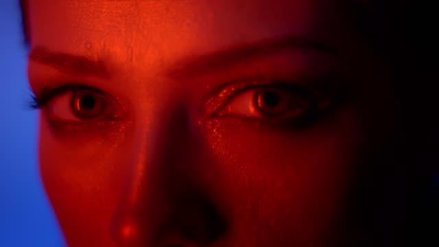 close-up shot of eyes and lips of calm fashion model in red neon light watching fixedly into camera on blue background. - occhiata laterale video stock e b–roll