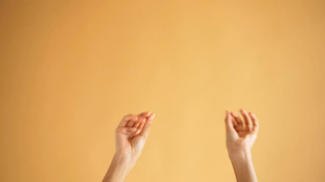 Close-up shot of female hands moving dancing snapping fingers then clapping Close-up shot of female hands moving dancing snapping fingers then clapping on orange background. Fun, good mood, arms gesture and playful people concept. snapping stock videos & royalty-free footage