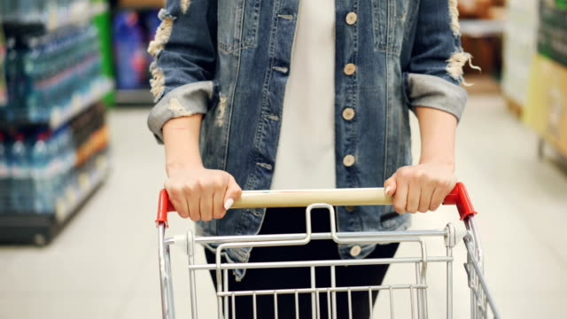 Close-up shot of female hands pushing shopping cart in supermarket, shelves with food and drinks are visible. Buying and choosing products and people concept. video