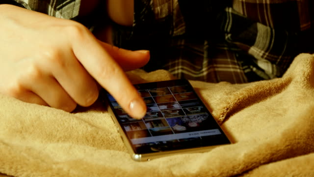 Close-up shot of female hands touching smartphone while lying on bed sheet. Scroll through the images on a smart phone; browse photos video