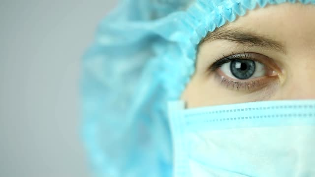 Close-up shot of female medical worker wearing face mask looking video